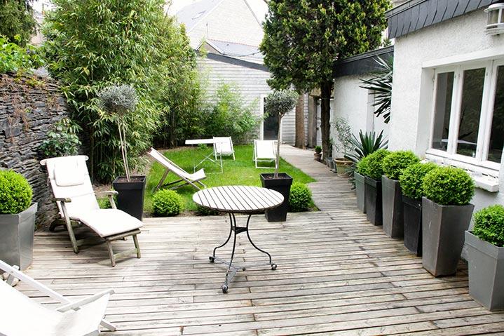 Une terrasse en bois nichée au coeur d'un jardin citadin.