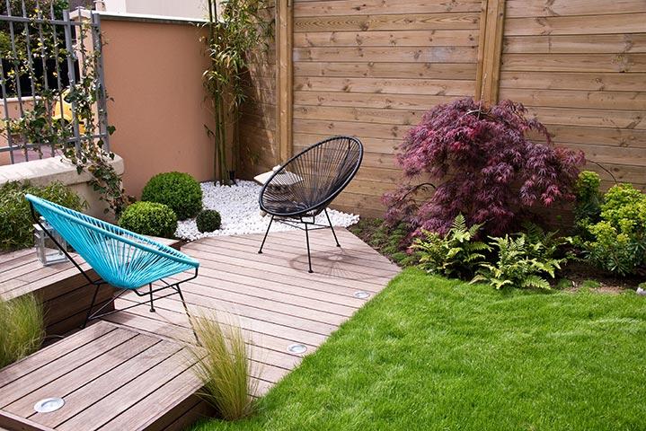 Un coin de jardin aménagée de deck et de verdure.