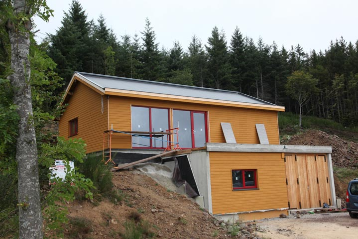 Maison bois sur un terrain de montagne
